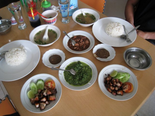 Batak cuisine, the saksang pork stew cooked in its blood and spices, and panggang grilled pork, with sayur daun singkong cassava leaf vegetables and broth soup.